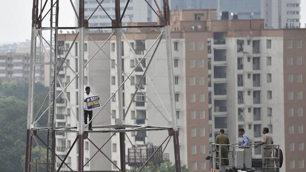 Fire fighters try to take down a man who climbed the Fire Station tower to demand special status for Andhra Pradesh at Connaught Place in New Delhi on Friday.(Sanchit Khanna/HT Photo)