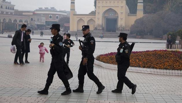 Uyghur security personnel patrol near the Id Kah Mosque in Kashgar in western China's Xinjiang region on November 4, 2017.(AP Photo)