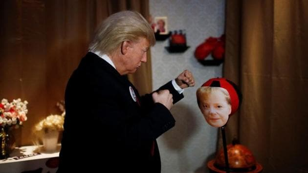 A performer in a Donald Trump mask hits a punching ball with German chancellor Angela Merkel's face at the Madame Tussauds wax museum in Berlin, Germany, on Tuesday.(REUTERS photo)