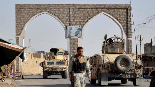 An Afghan security guard walks during a Taliban attack in Ghazni city, Afghanistan.(Reuters photo)