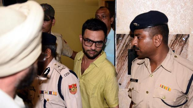 Delhi Police officers with JNU scholar Umar Khalid outside the Constitution Club soon after the incident in New Delhi on Monday.(Sonu Mehta/HT Photo)