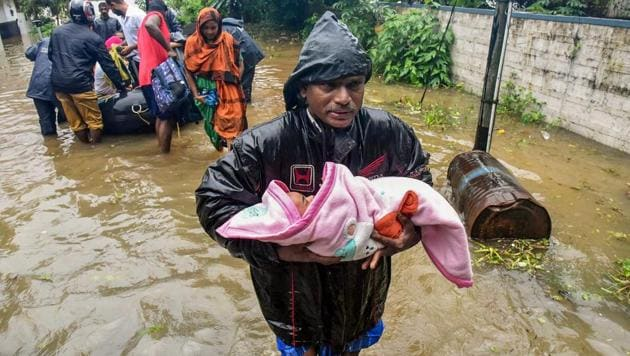A rescuer carries an infant as people are evacuated from a flood-hit locality in Kochi on August 15, 2018.(PTI)