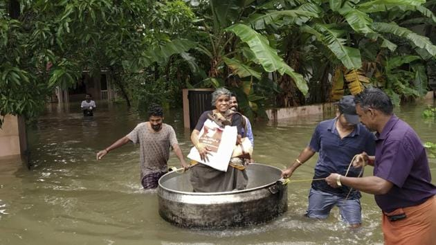 An elderly woman is rescued in a cooking utensil after her home was flooded in Thrissur, Kerala.(AP Photo)