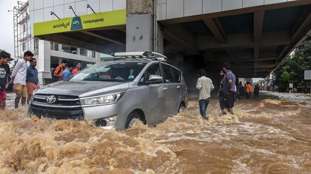 People wade across a waterlogged street at a flood-affected region following heavy monsoon rainfall, in Kochi.(PTI Photo)