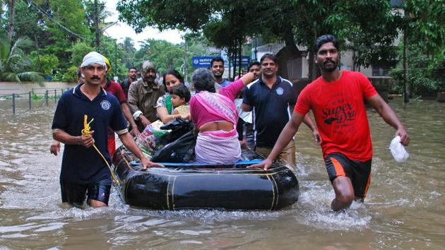 Volunteers and rescue personnel evacuate local residents in a boat in a residential area at Kozhikode, in the Indian state of Kerala, on August 16, 2018.(AFP)