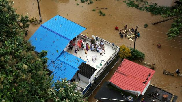 People wait to be rescued atop their house in a flooded region of southern Kerala on Friday.(REUTERS Photo)