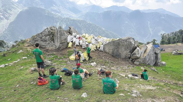Members of Waste Warriors, a Dharamshala-based NGO, collect the litter left behind by trekkers along the Triund trail.(Burhaan Kinu/HT PHOTO)