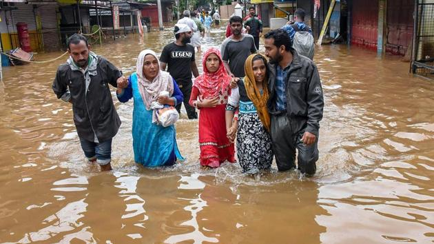 People wade across a waterlogged street after being rescued from flood-affected regions following heavy monsoon rainfall in Kochi.(PTI Photo)