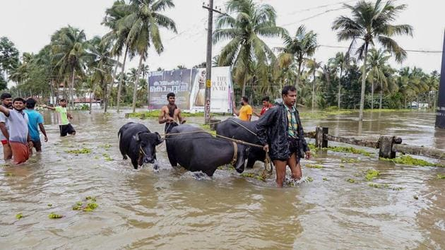 People wade across waterlogged streets as heavy monsoon rains causes floods, at Malappuram in Kerala on Saturday, Aug 18, 2018. Between August 1 and 19, the state received 758.6 mm of rainfall, against the average of 287.6 mm, or 164% more.(PTI)