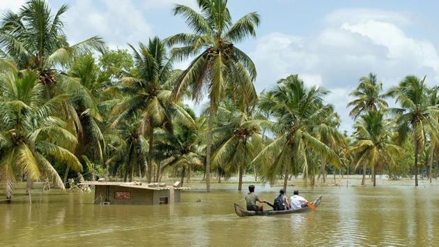 Men take a small boat to travel across flood waters past a marooned farm building to reach their homes in Pandanad in Alappuzha district in Kerala on August 21.(AFP Photo)
