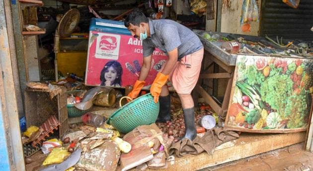 A man salvages the items at his shop after flood water receded at North Paravoor in Kochi on August 20, 2018.(PTI)