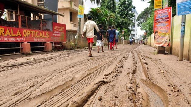 People walk along a muddy road in Kochi, Kerala, August 20, 2018(AFP)