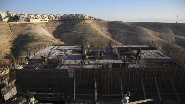 FILE - In this Feb. 7, 2017 file photo, Palestinian laborers work at a construction site in the Israeli settlement of Maale Adumim, near Jerusalem. Wm(AP)
