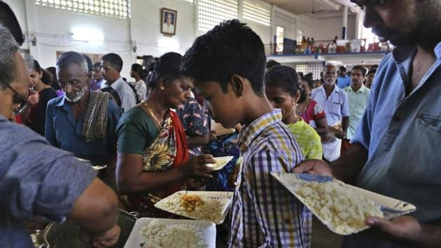 Flood-affected people receive food at a relief camp set up inside a school in Kochi in Kerala on August 23, 2018.(AP)