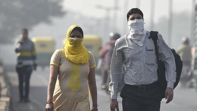 Commuters seen wearing face mask to avoid thick smog, as the air quality deteriorated sharply overnight leading to poor visibility conditions across the city, in New Delhi.(HT File Photo)