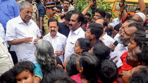 Kerala chief minister Pinarayi Vijayan interacts with the flood-affected people at a relief camp in Ernakulam.(PTI File Photo)