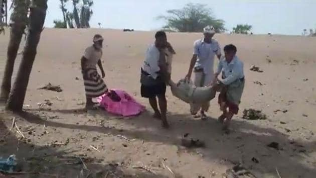 A grab taken from a AFPTV video on August 25, 2018 shows men carrying covered bodies in Al-Durayhimi, some 20 kilometers (12 miles) south of Hodeida, after a missile strike for which the Huthi rebels and a Saudi-led coalition fighting them traded blame.(AFP)