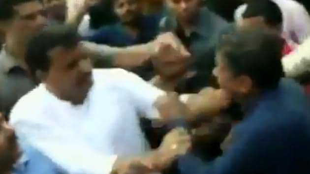 Congress MLA Umang Singhar (in white shirt) seen attacking a BJP leader in Dhar on August 25.(ANI/Screengrab)