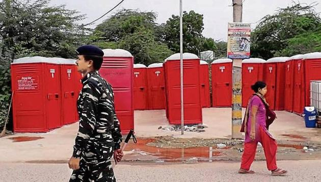 A security official (left) on Saturday patrols the area near the porta-cabins where the nine-year-old was allegedly raped in south Delhi's Rangpuri Pahari area.(Vipin Kumar/HT PHOTO)