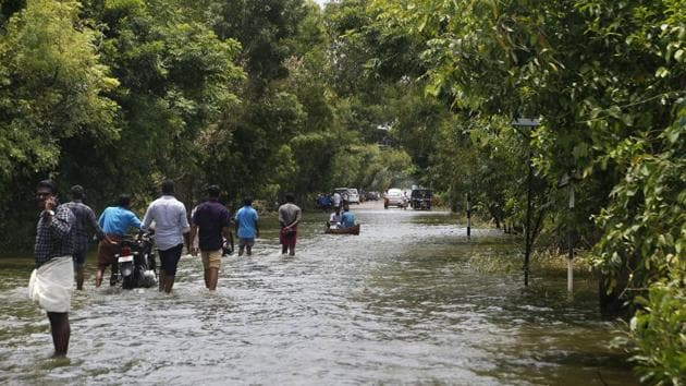 People wade across a waterlogged street in a flood-affected area, in Alleppey.(PTI)