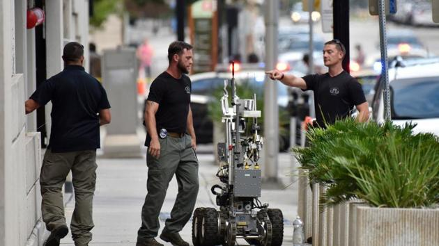 Bomb squad police prepare a robot to enter a parking garage a block away from the scene of a multiple shooting at the Jacksonville Landing on Sunday.(AP)