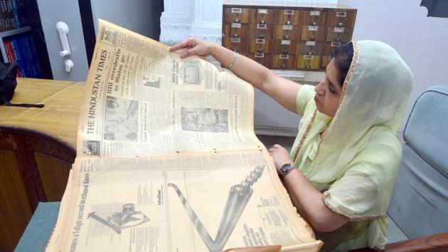 A woman employee examining the condition of the file of old issues of Hindustan Times newspaper at Sikh Reference Library at Golden Temple.(HT Representative Photo)