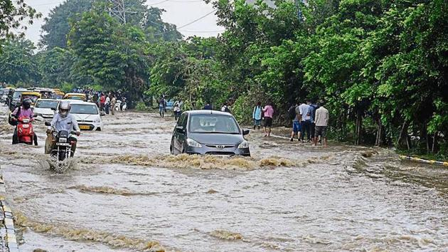 Commuters wade through a waterlogged street in Sector 44, on Tuesday.(Sanjeev Verma/HT PHOTO)