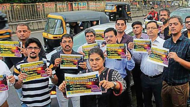 Residents of Ghodbunder Road staged a protest against bad roads last Friday by lining up their cars and blinking their headlights while commuting in a single file to Bhandup.(Praful Gangurde/HT)