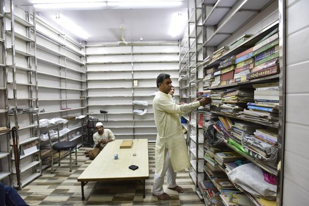 Mohammad Naeem, co-founder of Hazrat Shah Waliullah Library supervises the restocking of the new shelves, part of library's renovation.(Mohd Zakir/HT PHOTO)