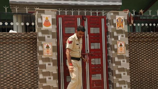 A policeman comes out of the house in Brijpura, Pataudi, where four members of a family were murdered on Wednesday.(Parveen Kumar / HT Photo)