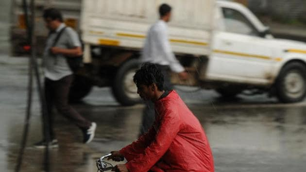 Commuters caught in the rain at Hero Honda Chowk in Gurugram. (Parveen Kumar/HT Photo)