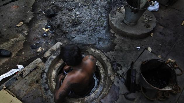Municipal worker attempts to unblock a sewer, New Delhi, October 7, 2009(Raj K Raj / Hindustan Times)