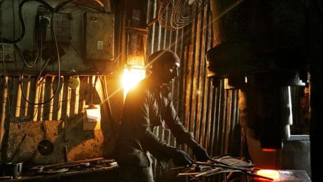 A worker operates a hydraulic press machine at a workshop manufacturing flanges for automobiles in Mumbai.(REUTERS)