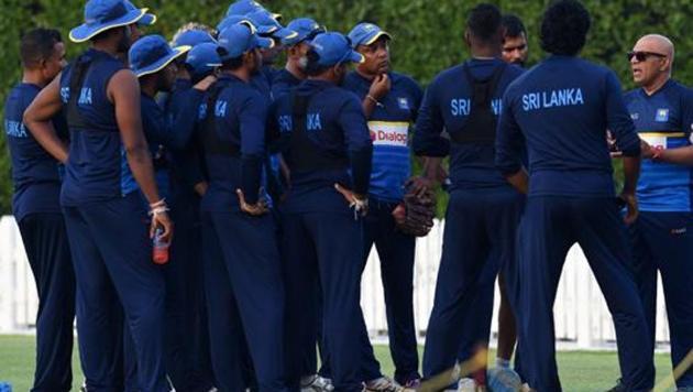 Sri Lankan coach Chandika Hathurusingha (3R) talks with team members during a training session in Dubai.(AFP)