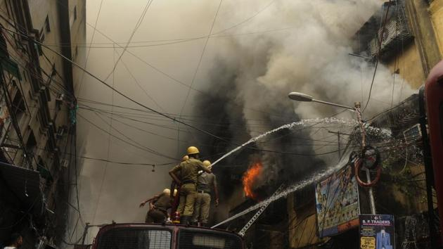 Firefighters trying to douse the fire at Bagri Market, at Burrabazar, in Kolkata on Sunday. The fire is still blazing on Monday morning.(Samir Jana/HT photo)