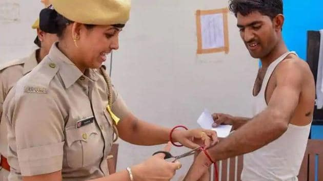 A police personnel removes a wristband of a candidate before entering the examination centre for the Rajasthan Police Constable Recruitment Exam 2018 in Bikaner.(PTI FIle Photo)