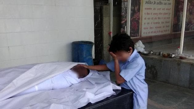 A photograph this reporter had tweeted on Monday of Anil's son, Gaurav, 11, weeping next to his father's body at a Delhi crematorium, had moved the Twitterati to raise the money for the family.(HT Photo)