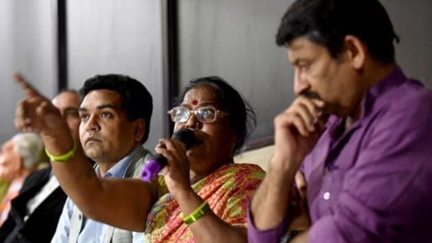 Kalawati Koli, mother of AAP worker Santosh Koli, speaks as MLA Kapil Mishra and BJP MP Manoj Tiwari look on, during a press conference at his residence in New Delhi on Tuesday.(Amal KS/HT PHOTO)