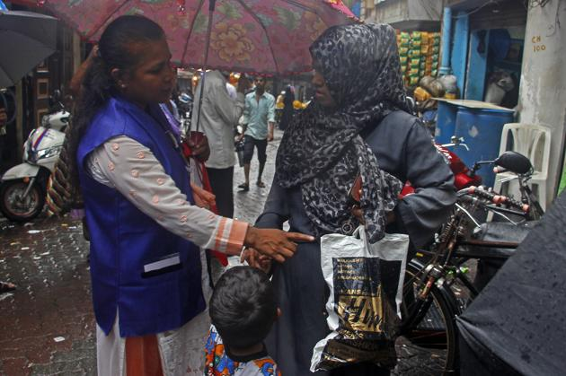 A BMC official makes a local women understand the harmful effect of using plastic bags at Keshavji Nayak road near JJ Hospital in Mumbai.(HT PHOTO)