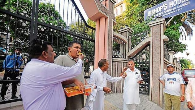 Members of Punjab Christian Movement distributing sweets to each others outside Sacred Heart Catholic Church in Jalandhar on Friday.(HT Photo)