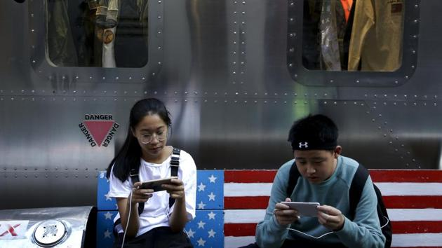 Shoppers sit on a bench with a decorated with US flag browsing their smartphones outside a fashion boutique selling U.S. brand clothing at the capital city's popular shopping mall in Beijing. China raised tariffs Monday on thousands of US goods in an escalation of its fight with President Donald Trump.(AP)