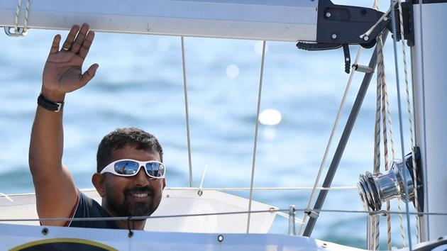 """Abhilash Tomy gestures on his boat as he sets sails from Les Sables d'Olonne Harbour at the start of the solo around-the-world """"Golden Globe Race"""" ocean race.(AFP File Photo)"""