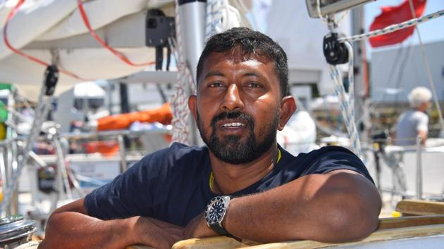 """India's skipper Abhilash Tomy poses on his boat """"Thuriya"""" in Les Sables d'Olonne Harbour, ahead of the solo around-the-world sailing race for the """"Golden Globe Race"""" ocean race in which sailors compete without high technology aides such as GPS or computers.(AFP File Photo)"""