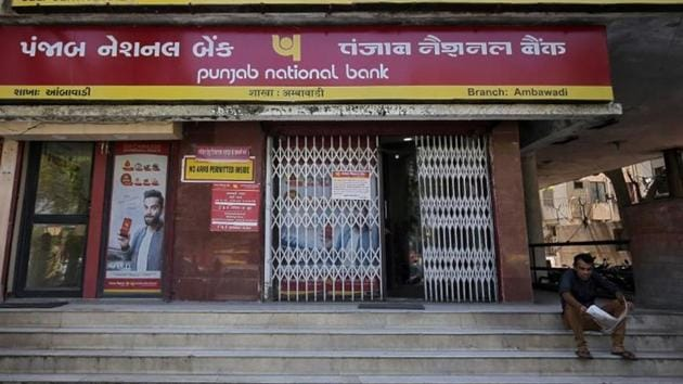 A man reads a newspaper outside a branch of Punjab National Bank (PNB) in Ahmedabad on March 20.(Reuters)