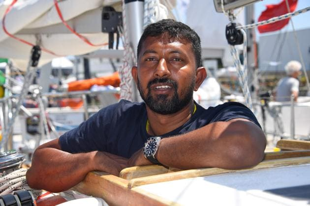 """Abhilash Tomy poses on his boat """"Thuriya"""" in Les Sables d'Olonne Harbour, ahead of the solo around-the-world sailing race.(AFP File Photo)"""