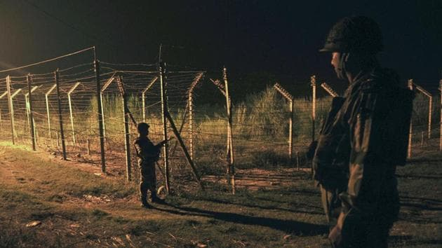 Border Security Force (BSF) soldiers standing guard during a night patrol near the fence at the India-Pakistan International Border at the outpost of Akhnoor sector, about 40 km from Jammu.(HT File Photo)