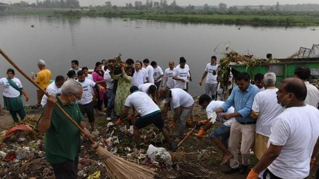 Residents of east Delhi along with BJP workers and its youth wing members cleaning up the Yamuna river.(HT Photo)