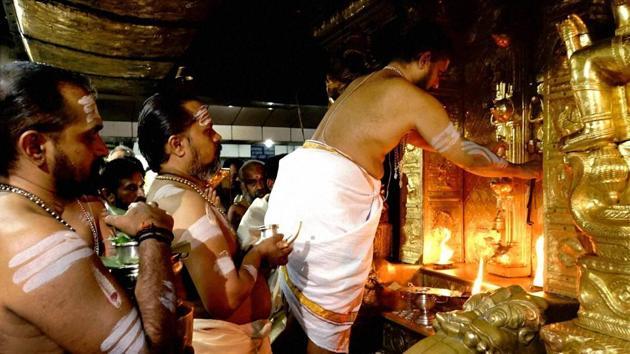 Sabarimala chief priest Unnikrishnan Namboothiri opens sanctum sanctorum at Lord Ayyappa temple at Sannidhanam in Sabarimala on Wednesday.(PTI Photo)