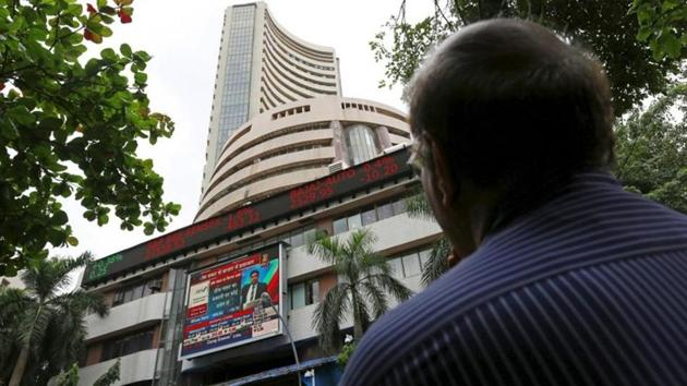 A man looks at a screen across a road displaying the Sensex on the facade of the Bombay Stock Exchange (BSE) building in Mumbai.(REUTERS)