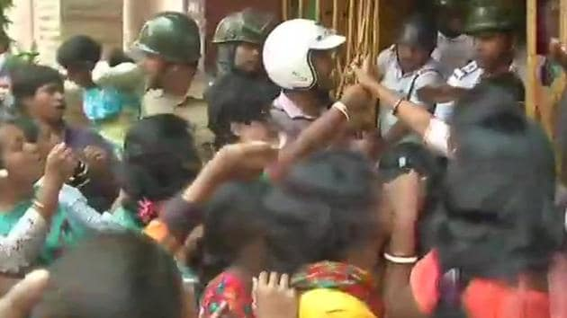 Police attempt to restrain agitating parents from entering a school in Dhakuria where a teacher allegedly molested a student in September.(ANI/Twitter)